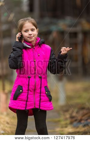 Little girl talking on phone standing in the yard.