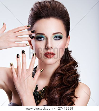 Beautiful woman with green make-up and creative color of nails