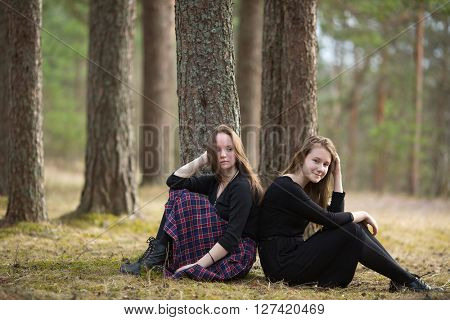 Girls girlfriends sitting together in a pine forest.