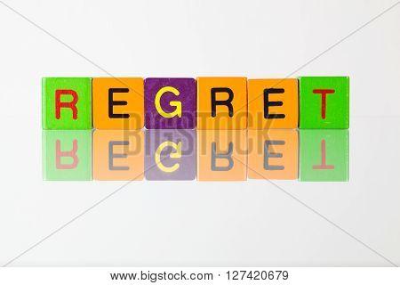 Regret - an inscription from children's wooden blocks