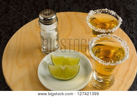 Two gold tequila shots with lime and salt on the round wood board. Tequila. Gold Mexican tequila. Tequila shot. Alcohol drink