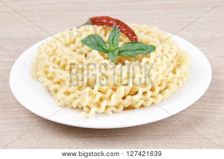 italian food : boiled pasta with basil and red pepper on white dish over wooden table
