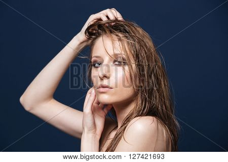 Beauty portrait of attractive woman with fresh skin looking at camera over blue background