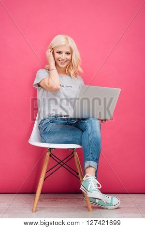 Lovely woman sitting on the chair with laptop computer on pink background