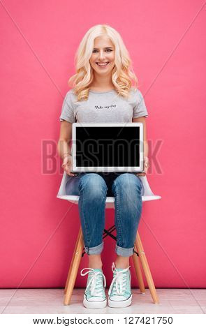 Smiling cute woman sitting on the chair and showing blank laptop computer screen on pink background