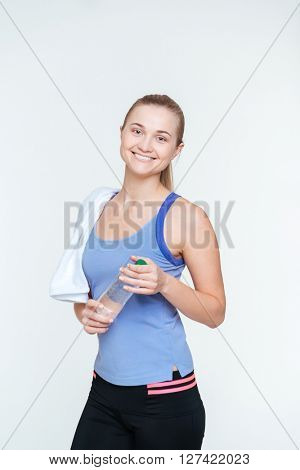 Smiling fitness woman with towel holding bottle with water isolated on a white background