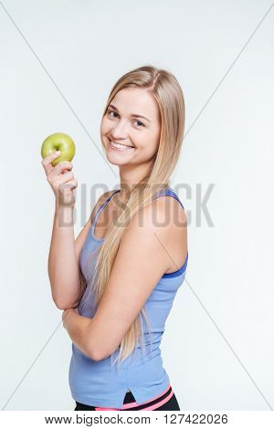 Happy sports woman holding apple isolated on a white background
