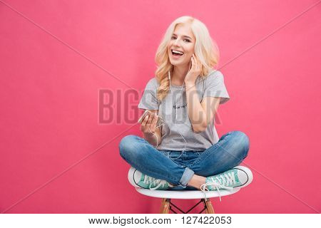 Cheerful woman listening music in headphones on smartphone over pink background