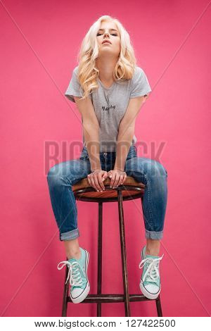 Cute blonde woman sitting on the chair and looking at camera over pink background