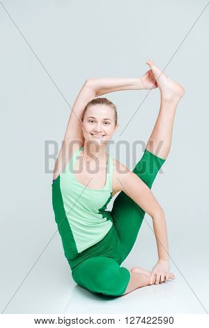 Smiling woman doing yoga exercise isolated on a white background