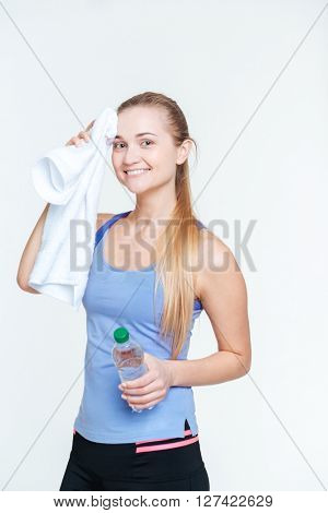 Happy woman holding towel and bottle with water isolated on a white background