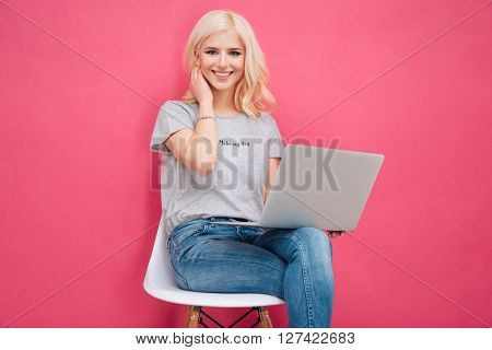 Attractive young woman sitting on the chair with laptop computer on pink background
