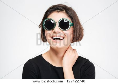 Laughing woman in sunglasses posing isolated on a white background
