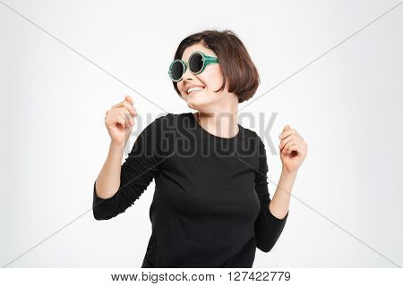 Smiling woman in sunglasses dancing isolated on a white background