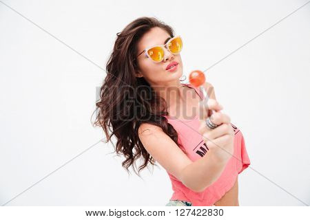 Lovely woman in sunglasses holding candy isolated on a white background