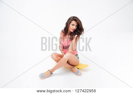Charming young woman sitting on the skateboard isolated on a white background