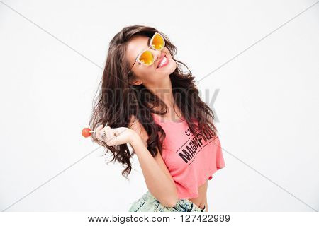 Stylish woman in sunglasses holding candy isolated on a white background