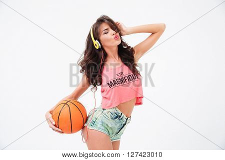 Sexy woman holding basketball ball and listening music in headphones isolated on a white background