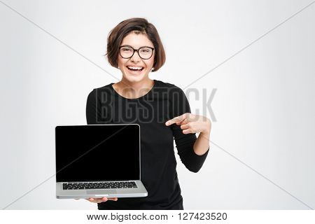 Laughing woman pointing finger on blank laptop computer screen isolated on a white background