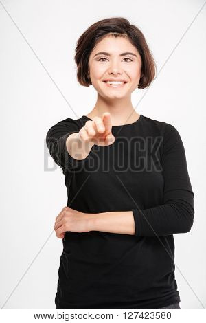 Smiling young woman pointing finger at camera isolated on a white background