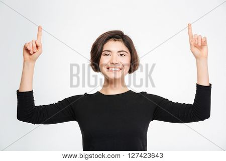 Happy woman pointing fingers up at copyspace isolated on a white background