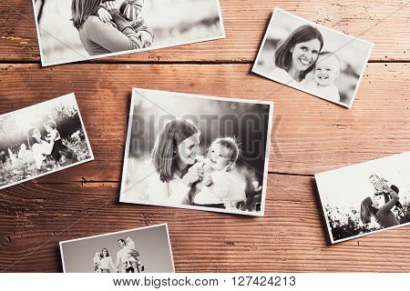 Mothers day composition. Various black-and-white family pictures. Studio shot on wooden background.