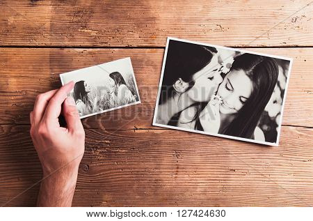Mothers day composition. Hand of unrecognizable man holding  black-and-white photo. Studio shot on wooden background.
