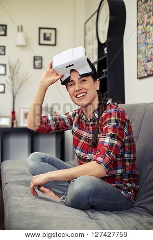 Smiling young woman sitting on the sofa in the lotus position, holding virtual reality glasses in the right hand