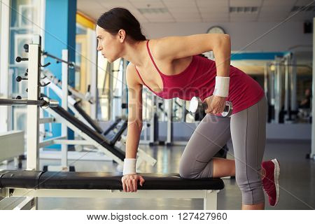 Woman is working out with dumbbells in gym and holds hands outstretched