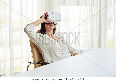 Young woman is smiling with her hand on virtual reality glasses