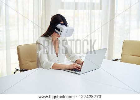 Young pretty woman is typing in virtual reality glasses while working on her laptop