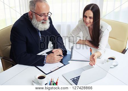 Businesswoman and businessman in a meeting discussing progress of the company