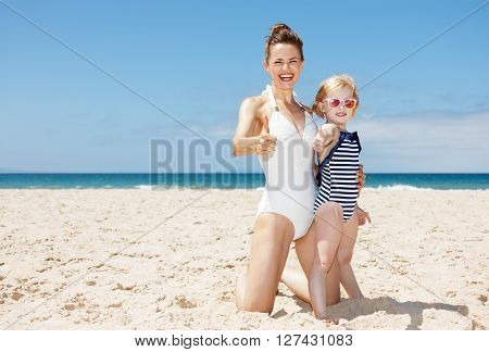 Happy Mother And Child In Swimsuits At Beach Showing Thumbs Up