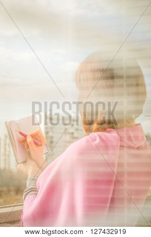 Woman making notes in the notebook vertical