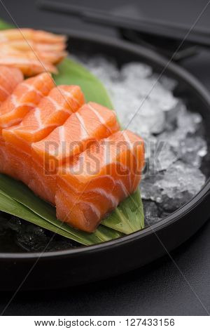 Japanese Cuisine. Salmon Sashimi On Ice Over Black Background.
