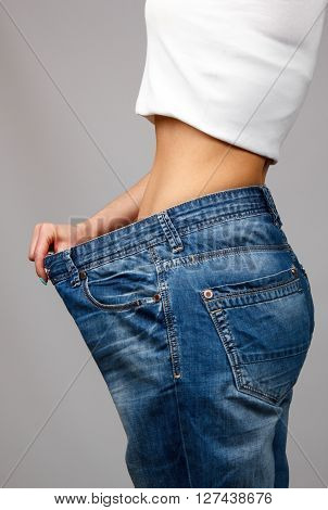 Slim girl trying on large size old jeans poster