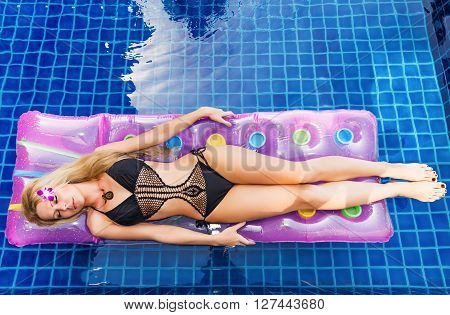 Young Pretty Blonde Woman On Air Mattress In Swimming Pool