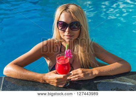 Young Pretty Blonde Woman In Swimming Pool With Water Melon Coctail Fresh Juice Drink
