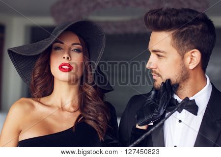 Sexy milf woman in hat with young lover in tuxedo in luxury flat