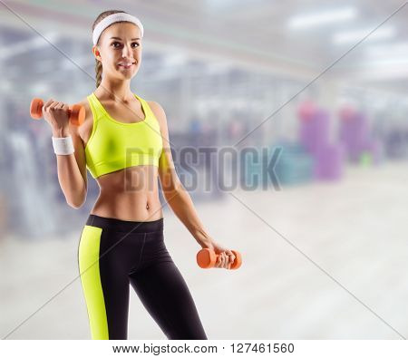 Young sporty girl with dumbbells in fitness club