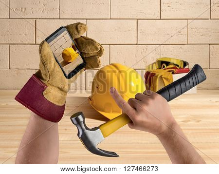 hand worker with hammer and smartphone, construction tools and helmet on brick wall background