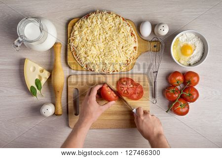 hands chefs cut tomatoes, cooking pizza ingredients on wooden background texture