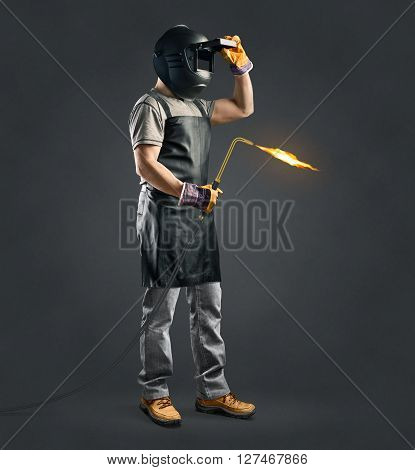 worker welder with gas welding machine on gray background poster