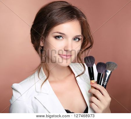 Makeup Artist Professional Stylist Woman Holding Brushes In Hand. Young Smiling Girl Posing At Camer