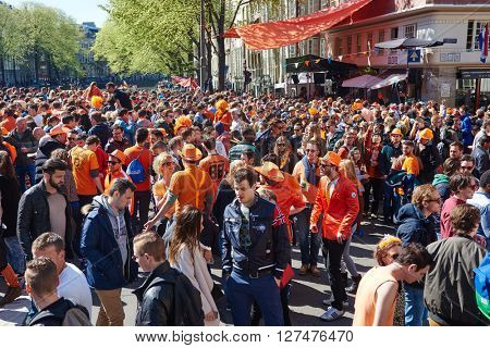 AMSTERDAM, NETHERLANDS on APRIL 26, 2015. City natives and tourists crowd during celebration Queen's Day or King's day, Dutch annual national holiday, in the streets of Amsterdam, Holland