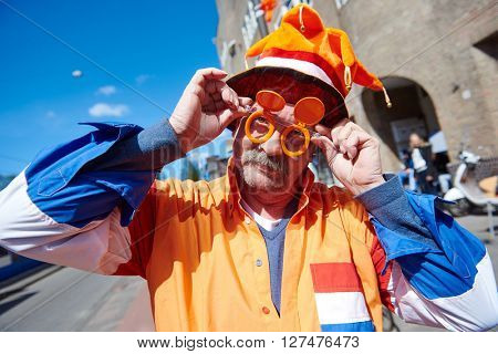 AMSTERDAM, NETHERLANDS on APRIL 26, 2015. Portrait of happy male city native tourist celebrating Queen's Day or King's day, Dutch annual national holiday, in the streets of Amsterdam, Holland