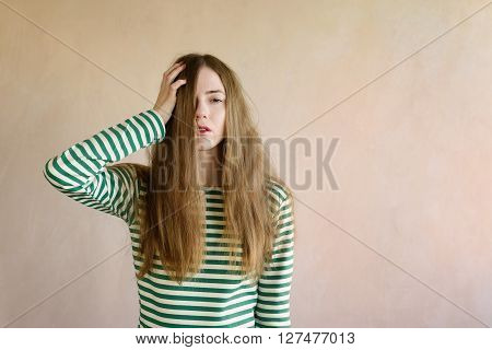 Sad dishevelled woman in a sailor's striped vest with a hand in her hair. Retouched color image.