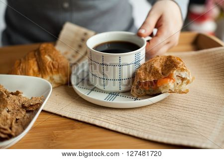 Healthy breakfast in bed with coffee, croissant, cornflakes and milk. Served tray with breakfast in bed. Woman having her breakfast in bed.