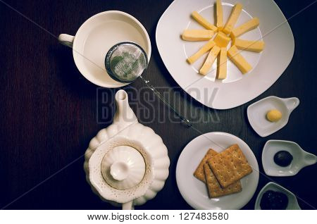 Plates of buiscuits and cheeses organized in star formation on dark wooden surface next to tea kettle, small plates with jam plus butter, shot from above angle.