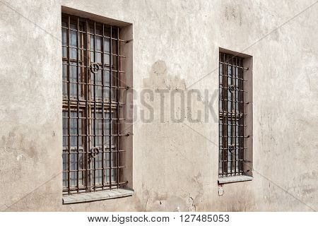 abandoned grunge cracked stucco wall with two window grilles